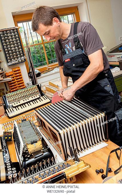 Instrument maker repairing bellow of accordion in repair shop