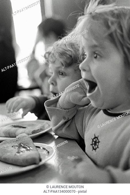 Children sitting at table, mouths open, side view, b&w