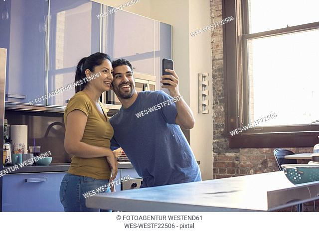 Young couple in kitchen taking selfie
