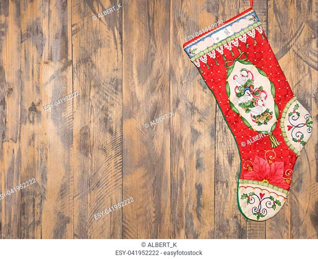 decorative red boot hanging on wooden background. christmas decorations