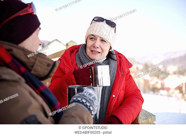 Mature couple with hot drinks talking outdoors in winter