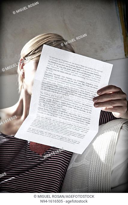 Young woman relaxing, reading a personal letter to the sunlight coming through the bedroom window