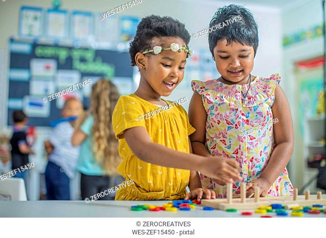 Two girls playing a game in kindergarten