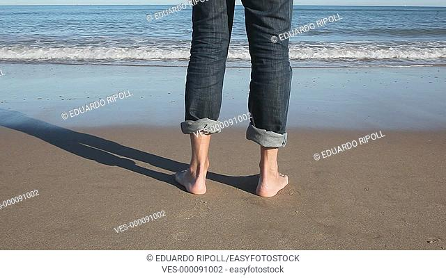 closeup of bare feet walking on the beach