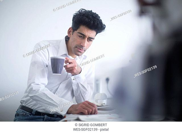 Portrait of businessman drinking coffee while reading newspaper in the morning at home