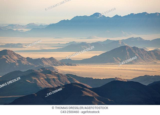 Isolated mountain ridges at the edge of the Namib Desert. Aerial view from a hot-air balloon. NamibRand Nature Reserve, Namibia