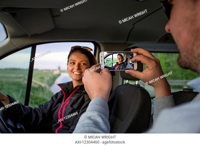 A man takes a photograph of a young woman with a smart phone while sitting in a vehicle; Egmond aan Zee, Holland