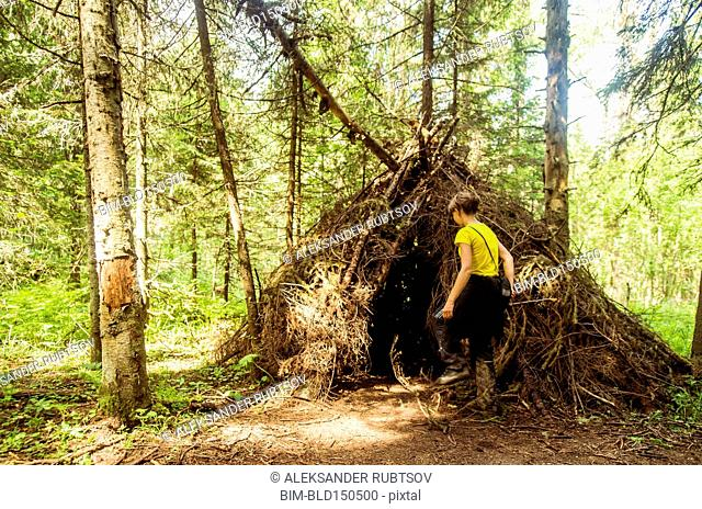 Caucasian boy playing in thatched teepee fort in forest