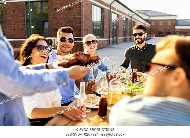 friends at barbecue party on rooftop in summer