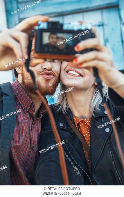 Young couple taking a selfie with vintage camera