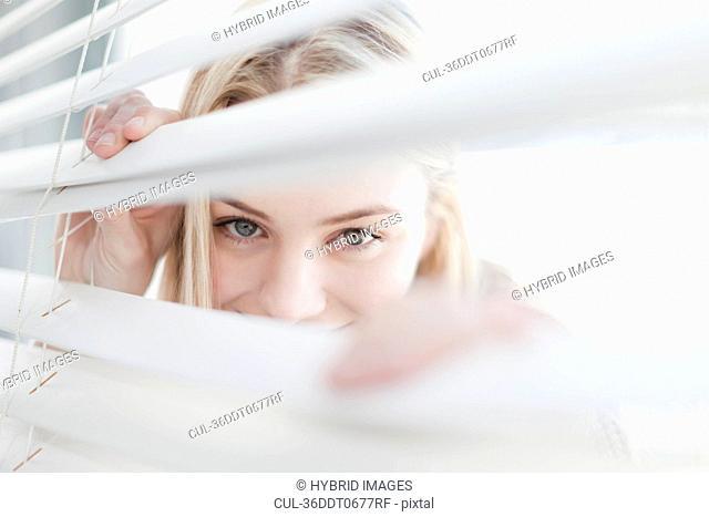 Teenage girl peering through blinds
