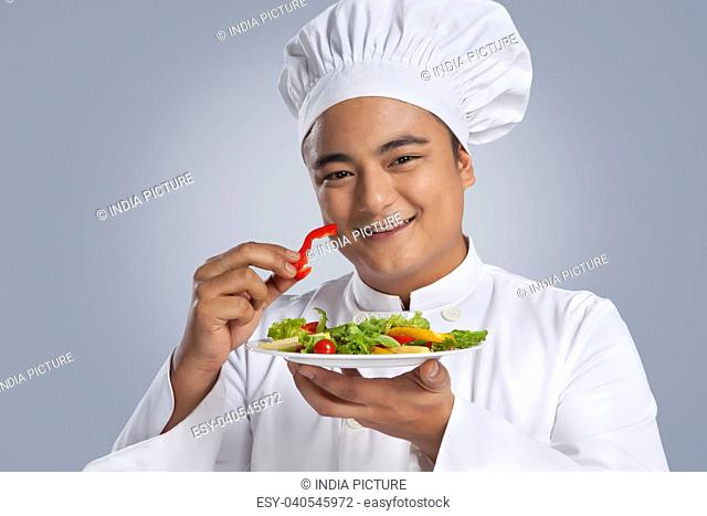 Portrait of chef with plate of vegetables