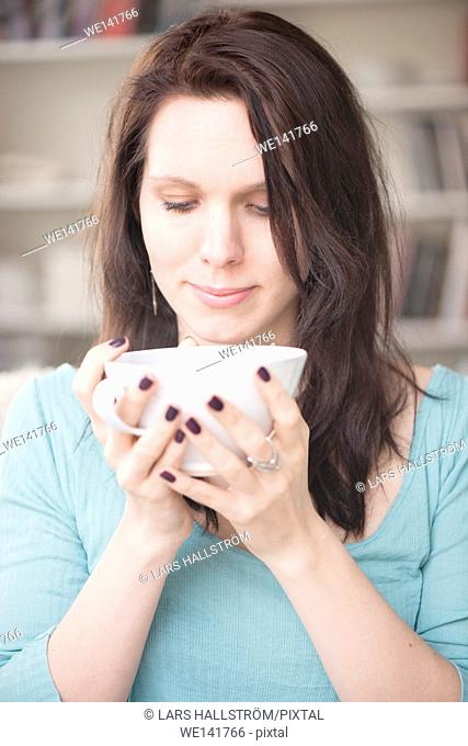 Woman holding tea cup in home interior. Concept of relaxation, taking a break and tranquility. Lifestyle image of contemplation