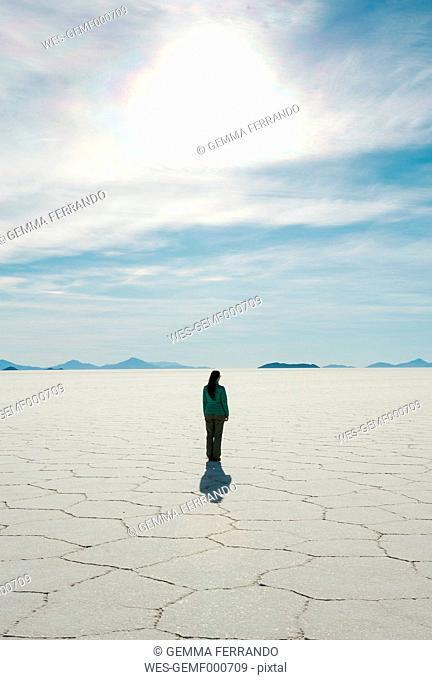 Bolivia, Atacama, Altiplano, Woman standing in Salar de Uyuni