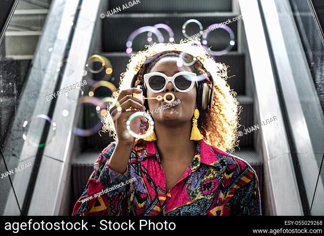 Stylish black lady in wireless headphones and earrings sitting on escalator with pout lips while blowing colorful transparent bubbles in back lit