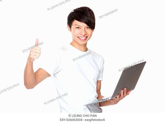 Young man use of notebook computer and thumb up