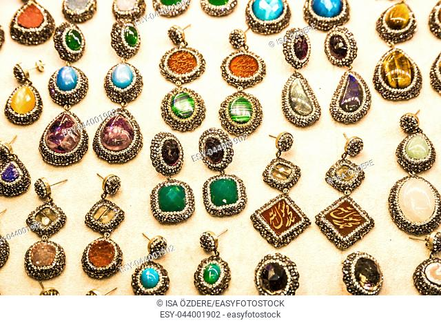 Many different color and shaped earrings with precious stones and gold on display for sale in Grand Bazaar, Istanbul, Turkey