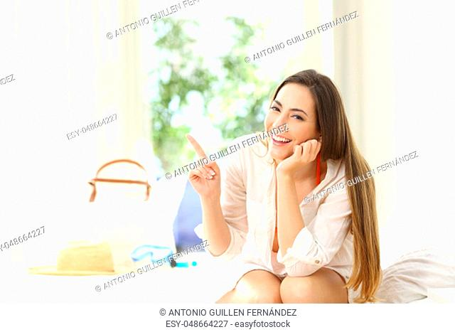 Happy hotel guest pointing at side and looking at camera sitting on a bed on summer vacations