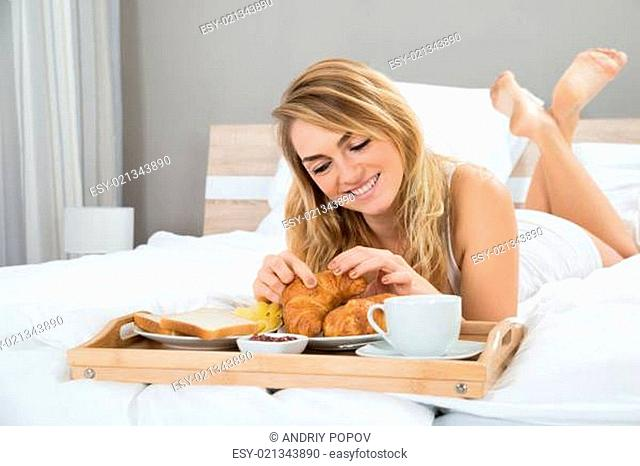 Young Woman Lying On Bed Having Breakfast