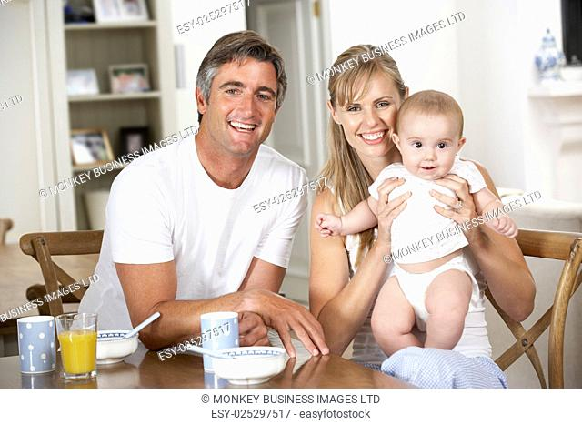 Family With Baby Having Breakfast In Kitchen Together