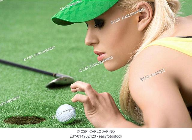 girl's playing with golf ball, she looks the ball