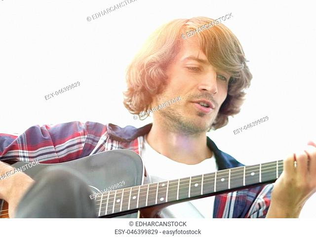 Handsome man playing on the guitar on the couch at home. concept of lifestyle