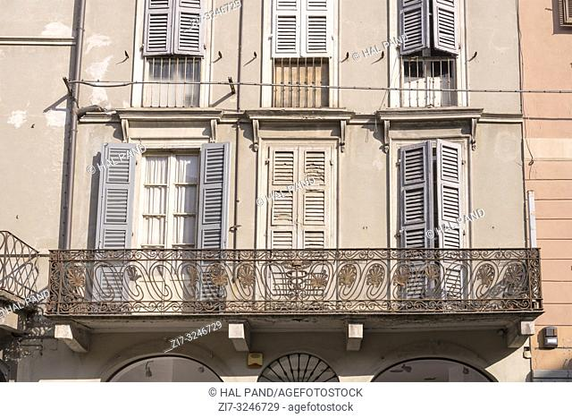 detail of art wrought iron railing on old balcony in city center, shot in bright winter light at Cremona, Lombardy, Italy