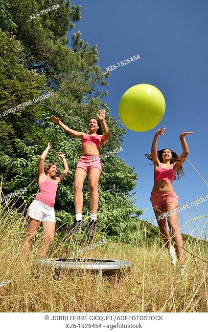 Three girls exercising with fitness ball at field