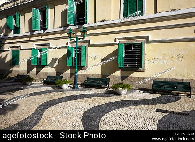 Traditional Portuguese wavy cobblestone street tiling in the historic district of Macau, China