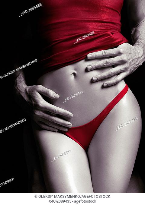 Man hands embracing young sexy woman in red underwear. Sensual couple artistically processed black and white photo