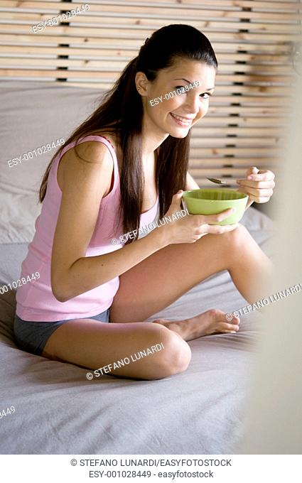 Teenage girl sitting on her bed and eating