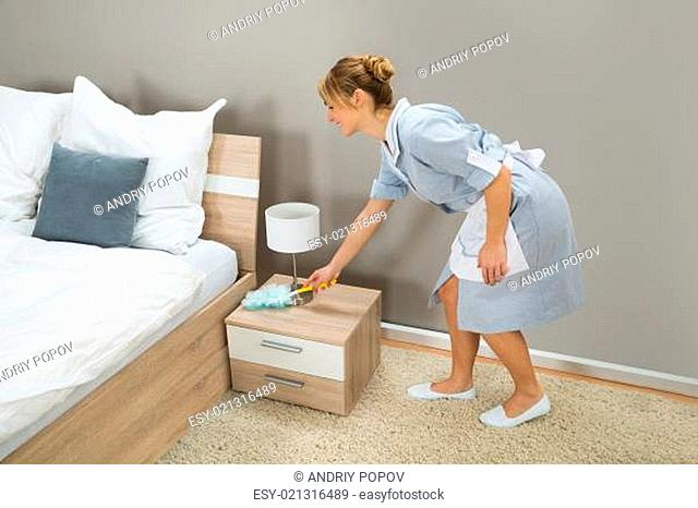 Young Happy Maid Cleaning Dust With Feather Duster In Hotel Room