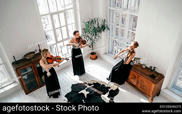 Three Women In Beautiful Dresses Are Playing Musical Instruments Inside Large And Bright Room With Big Windows