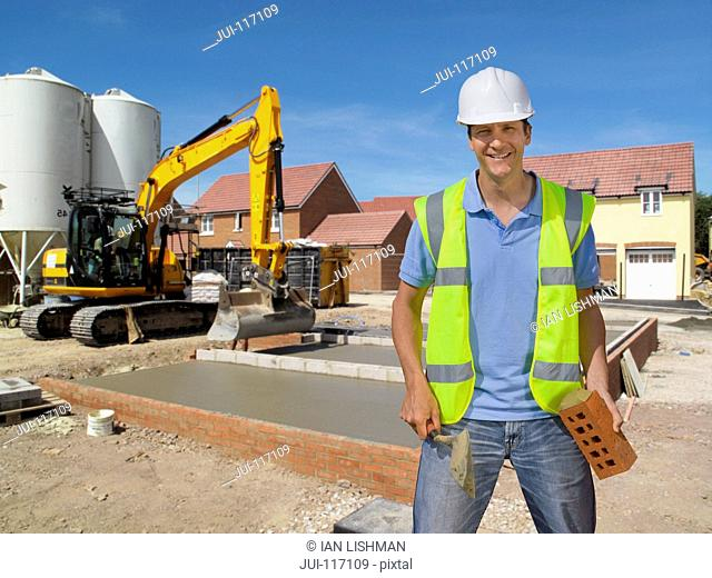 Portrait Of Bricklayer Working On Construction Site