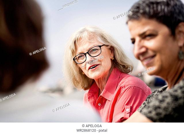 Smiling senior woman talking with friends outdoors