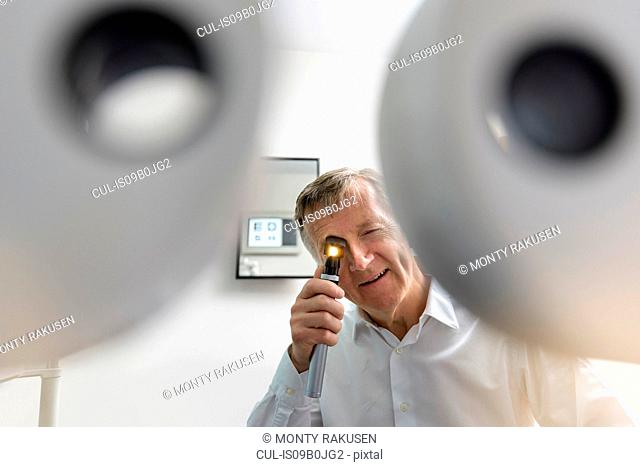 Optician looking into patient's eyes at small business opticians