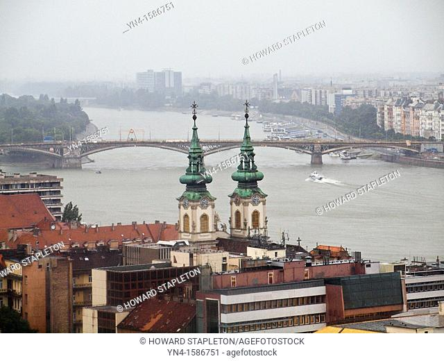 Budapest in the rain  The Danube River seperates Buda foreground from Pest  The twin spires of St  Anne Church are near the river in Buda