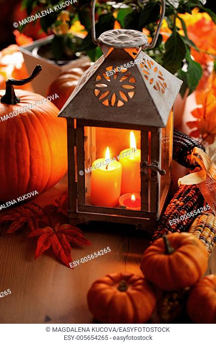 Lantern with candles, pumpkins and autumn decorations