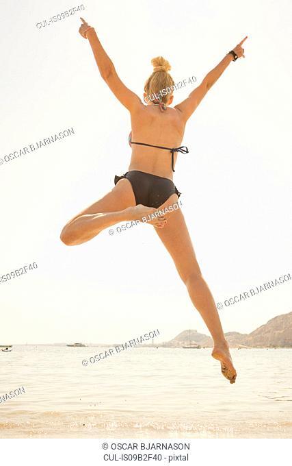 Rear view of woman in bikini jumping mid air on beach, Alicante, Spain