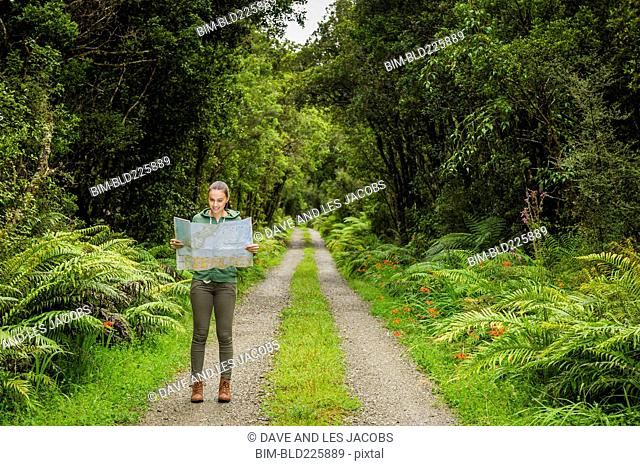 Hispanic woman reading map on path in lush green forest