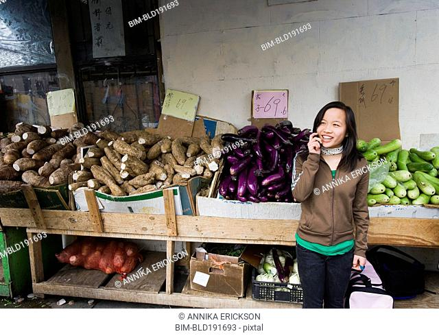 Chinese girl talking on cell phone at outdoor market