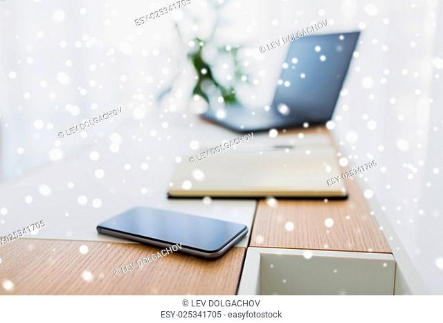 business, objects and education concept - office workplace with notebook, laptop computer and smartphone on table over snow