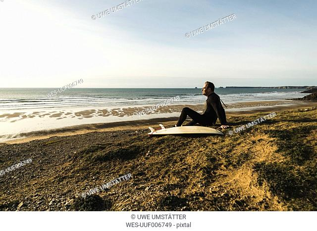 France, Bretagne, Finistere, Crozon peninsula, man sitting at the coast with surfboard