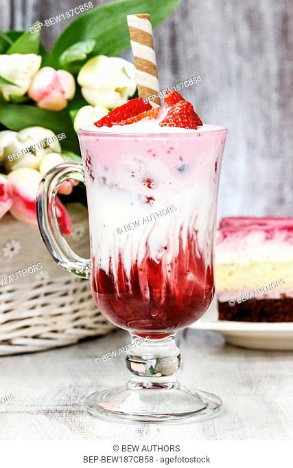 Strawberry milkshake and piece of cake in the background