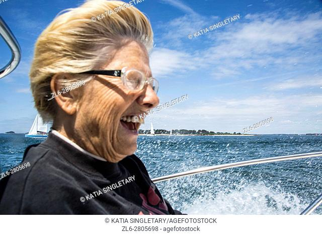 Caucasian retired senior, mature woman having fun and laughing during an outing on the boat in the ocean, in Brittany, France