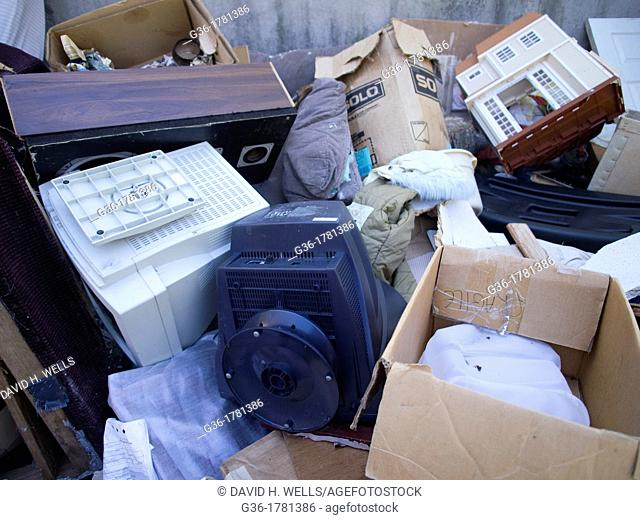 Computer monitors and trash pile up outisde a foreclosed house in Milbury, Masachussetts, United States