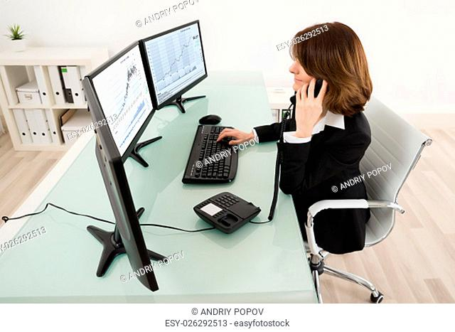 Young Female Stock Market Broker Working On Multiple Computers While Talking On Phone