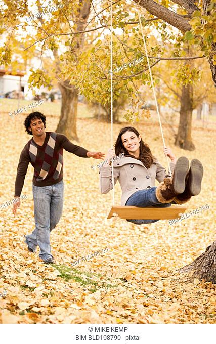Couple playing on swing in autumn leaves