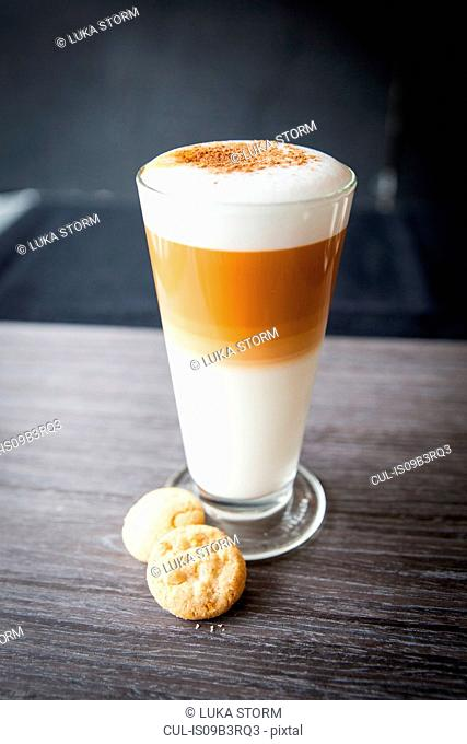 Glasses of latte macchiato and biscuits on table