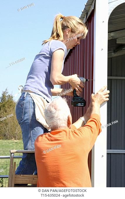 Woman and her father building a shed